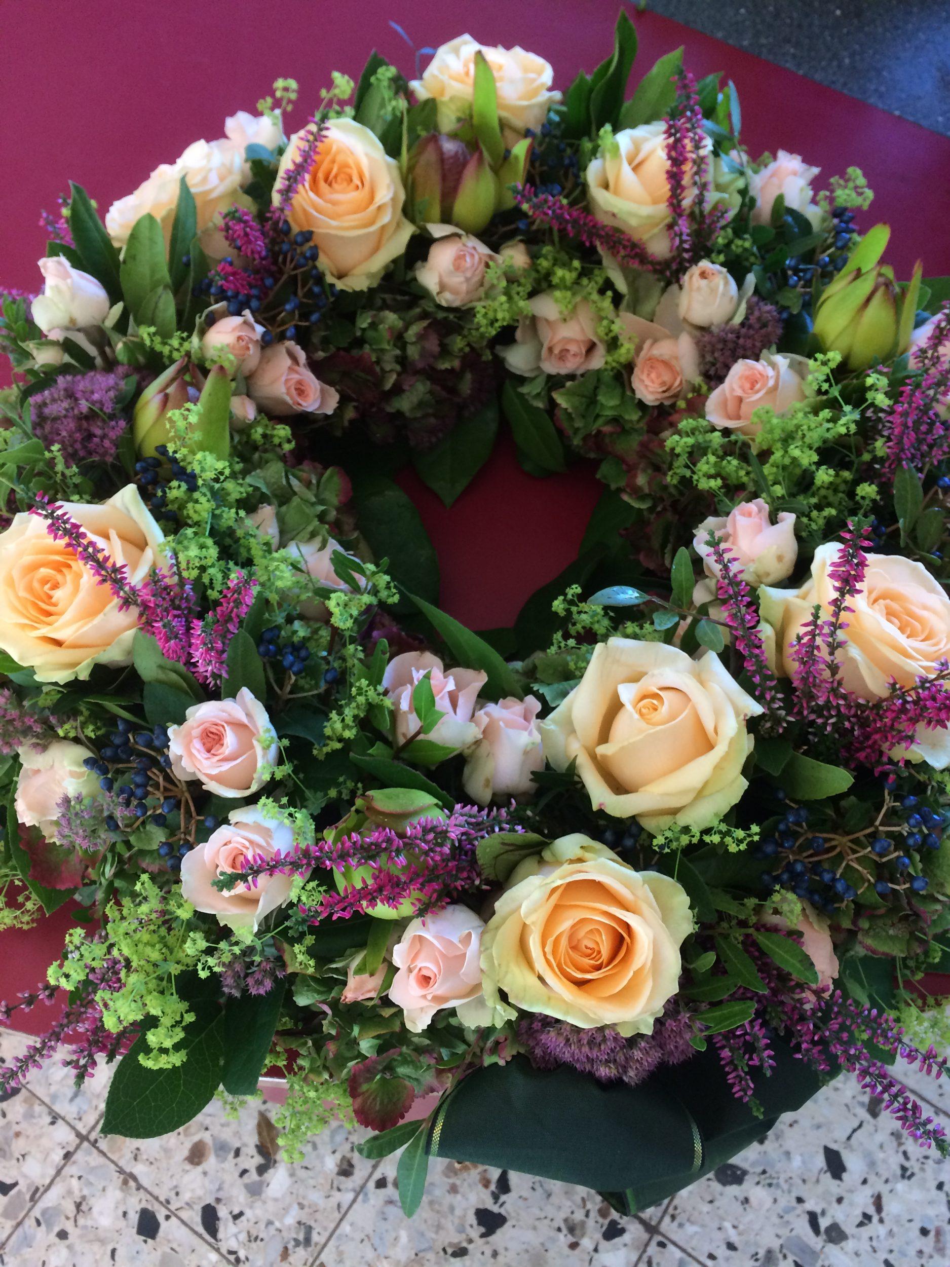 Trauerfloristik in Berlin: Trauergsteck mit weißen und lila Blumen, Trauerkranz