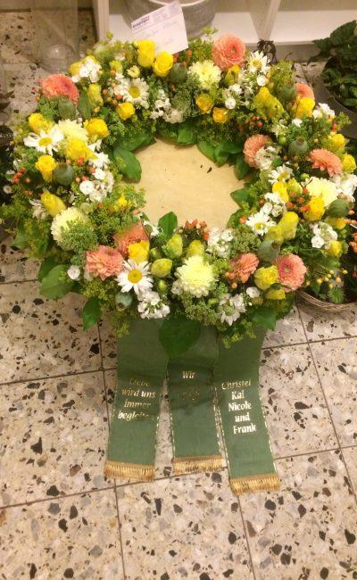 Trauerfloristik in Berlin: Trauergsteck mit weißen, rosen und gelben Blumen, Trauerkranz mit Schleife